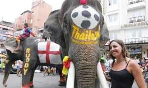 A tourist poses with an elephants during a World Cup promotion on Khao San Road in Bangkok.