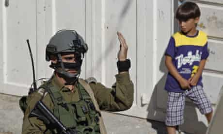 Palestinian boy watches Israeli soldier during search for three Israeli teenagers in West Bank