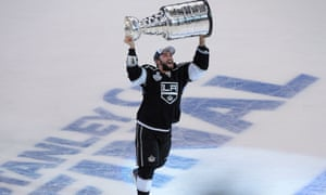 Los Angeles Kings defenseman Alec Martinez carries the Stanley Cup after beating the New York Rangers.