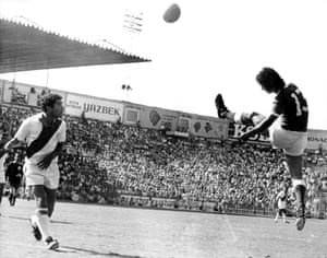 Peru's Hector Chumpitaz looks on as West Germany's Gerd Muller heads the ball back across the goal.