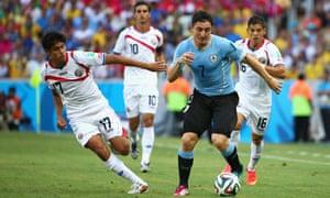 Cristian Rodriguez of Uruguay races away from Yeltsin Tejeda of Costa Rica.