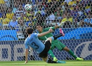 Uruguay's defender Diego Godin (L) loops the ball over Costa Rica's goalkeeper Keylor Navas.