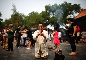 Beijing, China: A relative of a passenger aboard the missing Malaysia Airlines flight MH370 burns incense as he prays at Yonghegong Lama Temple.
