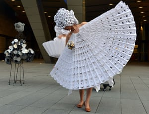 Tokyo, Japan: A model wears an origami dress designed by Diana Gamboa while standing next to sculptures by Gamboa's husband, Luis Fernando Bohorquez during a performance art piece, titled The Cyclops: a love story.