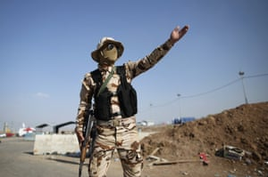Kalak, Iraq: A Peshmerga fighter directs traffic at a check point.