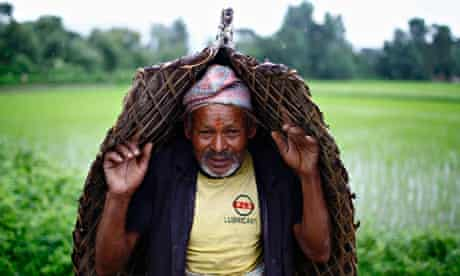 A farmer covers himself from the rain during Asar Pandra festival in Bhaktapur