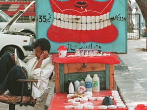 A roadside dentist reads newspaper in Karachi - where it is normal to charge between 0.75 to 4 US$ from minor toothache to major surgery