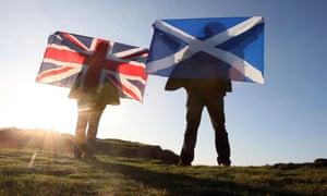 Scottish and British flags held up over Edinburgh, Scotland