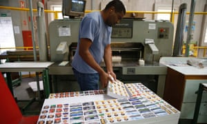 Cutting the stickers in a guillotine at the Panini factory.