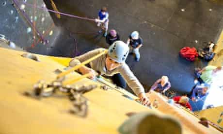 A young woman climbing a wall at an indoor rock climbing centre.