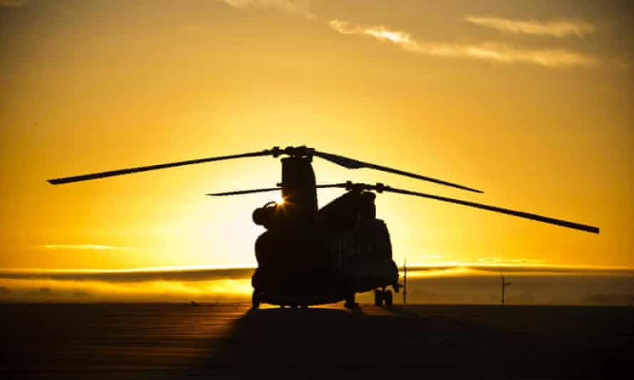 A British Royal Airforce (RAF) Chinook helicopter, during the sunrise, on the line at RAF Odiham.