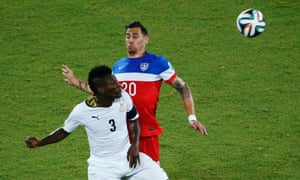 Ghana's Asamoah Gyan fights for the ball with Geoff Cameron