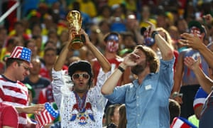 A United States fan dressed as Elvis holds up a replica of the World Cup at Estadio das Dunas in Natal.