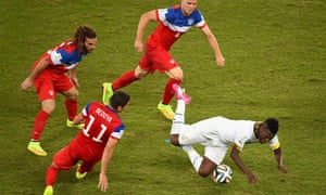 Asamoah Gyan of Ghana falls after a challenge by Alejandro Bedoya of the United States.