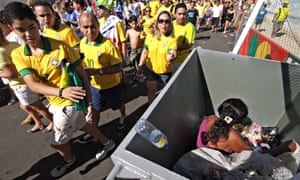 A woman collecting recyclables sitting in a garbage bin as football fans throw rubbish in the bin