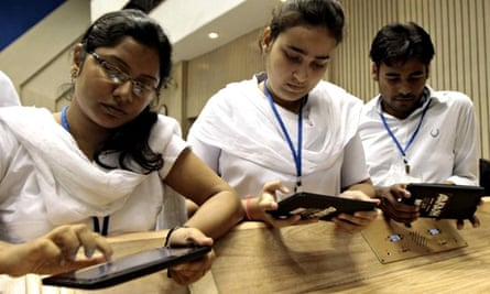 A group of students try the 'Aakash' tablet computer during a news conference in New Delhi, India