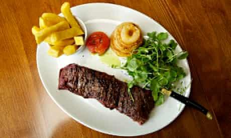 Slab of skirt steak with chips, salad, roast tomato