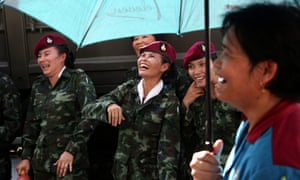 Thai soldiers and a woman, foreground, share a laugh during a 'Return Happiness to Thai People' at Bangkok's Victory Monument. Photograph: Apichart Weerawong/AP