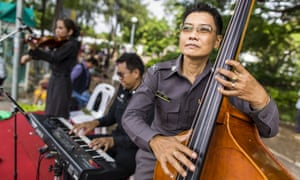 A Thai police jazz trio performs on a stage during a ''Return Happiness to Thais'' party in Lumpini Park.