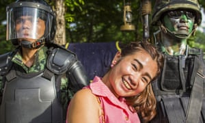 Woman smiles for photos with Thai military special operations soldiers the junta's public relations drive called 'Return Happiness to Thais'.