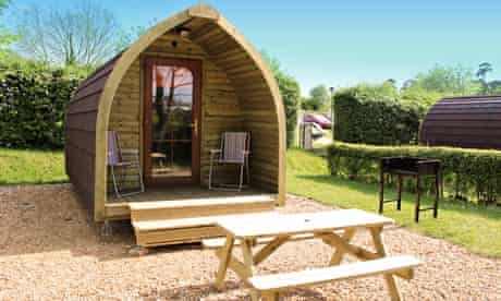 Wooden camping pod at Sandy Balls with picnic bench in front