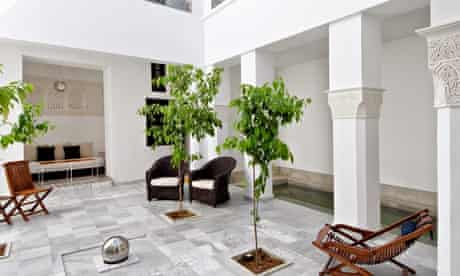 Courtyard with pillars, chairs, trees in Riad Sapphire in Marrakech