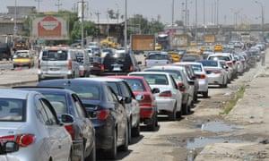 Iraqi motorists queue for fuel following an assault on Iraq's main Baiji oil refinery