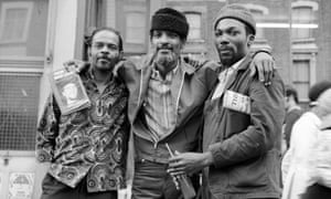 American Black Panther Party member Hakim Jamal (born Alan Donaldson, centre), on the Portobello Road, London, 1971. Jamal is holding a copy of his book 'From the Dead Level: Malcolm X and Me'.