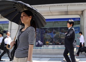 People walk by an electronic stock board of a securities firm in Tokyo,Thursday, June 19, 2014.
