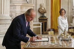 Spain's King Juan Carlos signs an abdication law in the presence of Queen Sofia during a ceremony at the Royal Palace in Madrid, Spain, on Wednesday