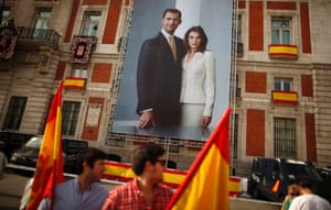 People holding Spanish flags walk past a poster showing Spain's new King Felipe VI and his wife Queen Letizia in Madrid.