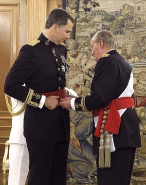 King Juan Carlos places the sash of the captain general of the armed forces on his son King Felipe VI of Spain in a ceremony held in the Hearing Room Zarzuela Palace