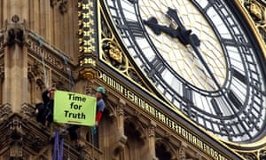 Two demonstrators from Greenpeace display a banner beneath the clock face of Big Ben, in central London on the first anniversary of the invasion of Iraq, March 20, 2004.