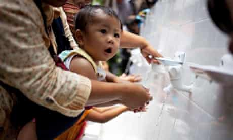 A mother help her baby to wash her hands in Jakarta, Indonesia