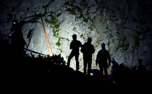 Rescuers wait for their deployment near a cable winch at the mouth of the cave, which was first discovered in 1995