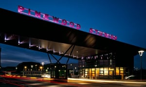 An impressive twilight view of Pinewood Studios, with letters lit in purple
