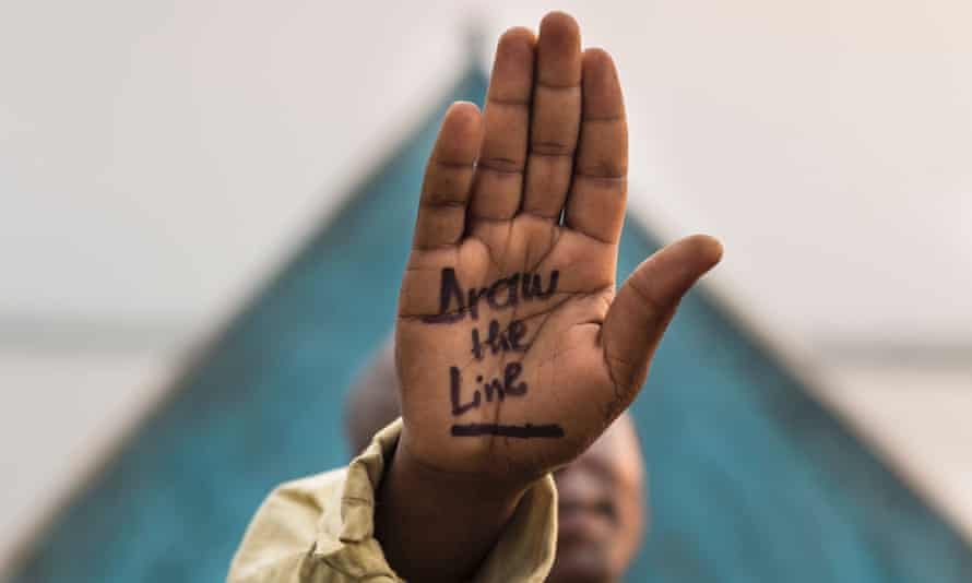 A villager with 'Draw the Line' written on his hand in objection to any oil prospecting, exploration or  drilling posing in Virunga National Park, Democratic Republic of Congo, as part of WWF's 'Draw the Line' Campaign.