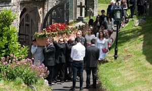 Rik Mayall's coffin is carried into the church in Dittisham, Devon, for his funeral