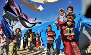 A Syrian woman carries her child at the Qah refugee camp along the Turkish border