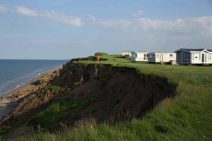 A dog walkeralong side a cliffside caravan park at Aldbrough.
