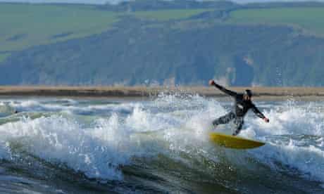 A surfer rides a wave off Bantham beach in Devon