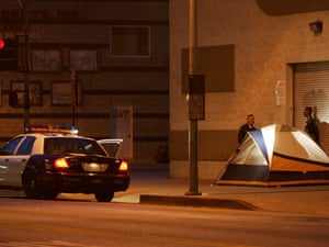 A police officer talks to a homeless man at his encampment on a downtown sidewalk los angeles