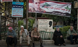 Syrans in Damascus sit beneath a banner of Bashar al-Assad ahead of the presidential election