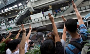 Protesters raise three fingers during an anti-coup demonstration in Bangkok on Sunday