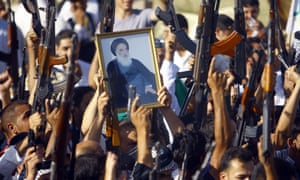 Iraqi Shias brandish their weapons and a picture of  Shia cleric Grand Ayatollah Ali al-Sistani as they gather to show their willingness to fight against Jihadist militants