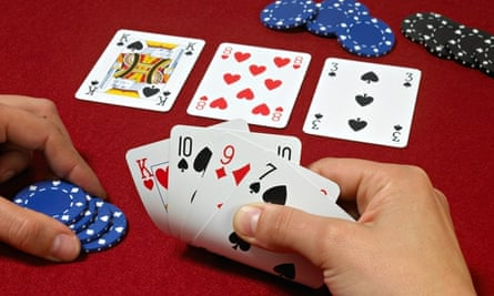 Poker hand with players hands against red baize