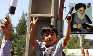 A boy holding a toy gun beneath a poster of Sha spiritual leader Grand Ayatollah Ali al-Sistani.