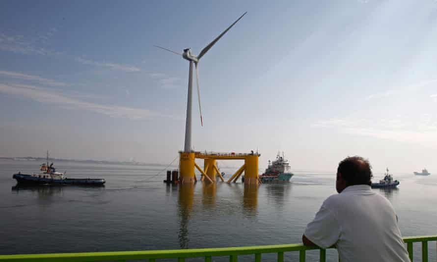 A ferry sailor watches the windmill, Wind Float I, at the Setubal city bay, 50 km (31 miles) south of Lisbon