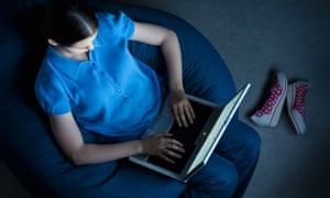 Teenager watching TV using a computer lifestyle entertainment leisure activity multi tasking teenager domestic scene