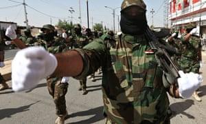 Armed Shia militiamen, followers of cleric Moqtada al-Sadr, parade in Kirkuk.